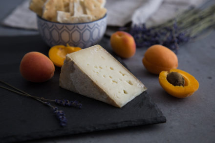 Apricots and Aged Goat Cheese on Slate Cheese Board with Crackers and Lavender