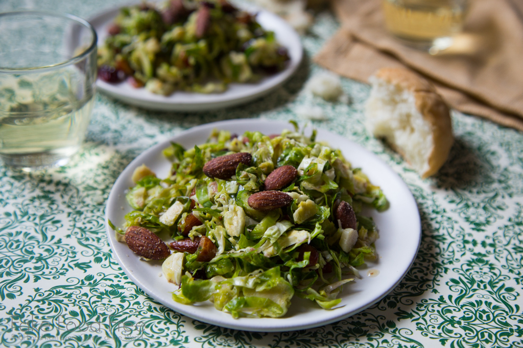 In this recipe for shredded Brussels Sprouts salad, the veggies are tossed with smoked almonds and cranberries and topped with an orange maple dressing | FakeFoodFree.com